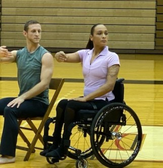 2 dancers in the Anne C. Steele Center performing, one female in a wheel chair, the other, male, sitting in a chair