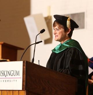 Kim Rothermel speaking a at podium in regalia attire