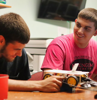 2 male students building a 3d printed remote control car that uses AI technology to drive