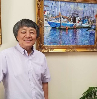 yan sun posing in front of one of his paintings