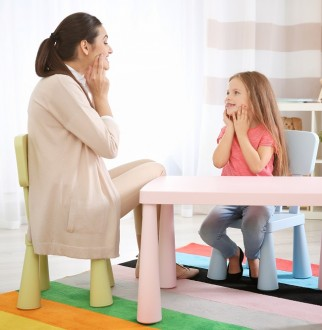 An Occupational Therapist working with a young girl at a child-friendly table.