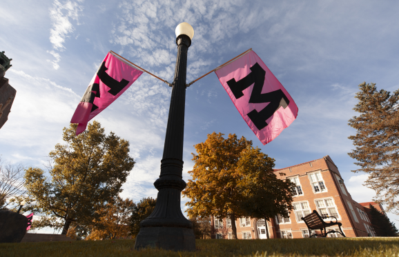 M flags on campus with fall trees