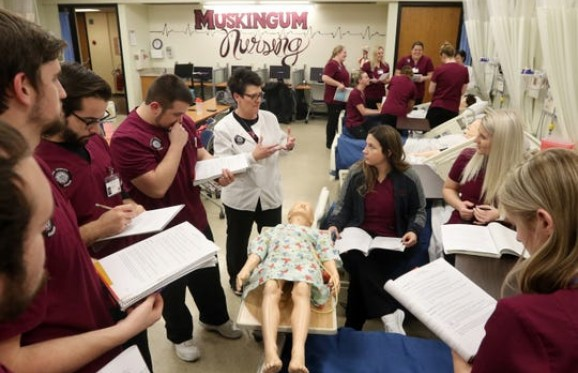 nursing class gathered around a hi fidelity simulation child dummy during class