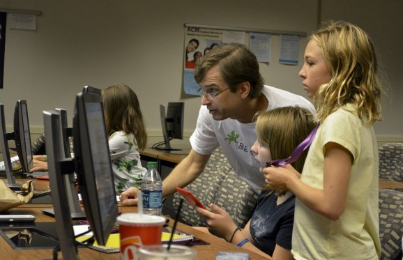 Professor Shaffstall working with students on a computer