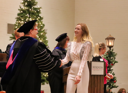 a blonde female student dressed in white crossing the stage and shaking hands with President Hasseler
