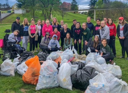 a group of students posing behind all the bags of trash that they collected