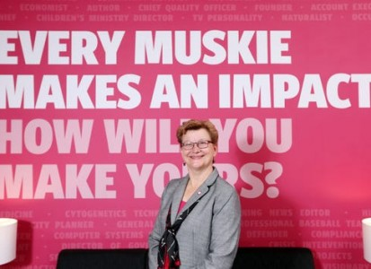 "susan hasseler posing in front of a wall with the text ""every muskie makes and impact.  How will you make yours?"""