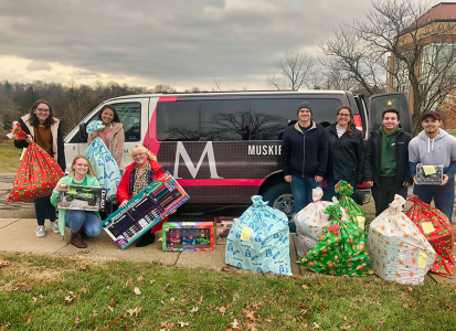 group shot of the students involve holding the gifts that they are donating.  Standing in front of the MU van, getting ready to load it full of toys.